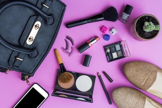 Make-up met decoratieve cosmetica en smartphone op roze achtergrond