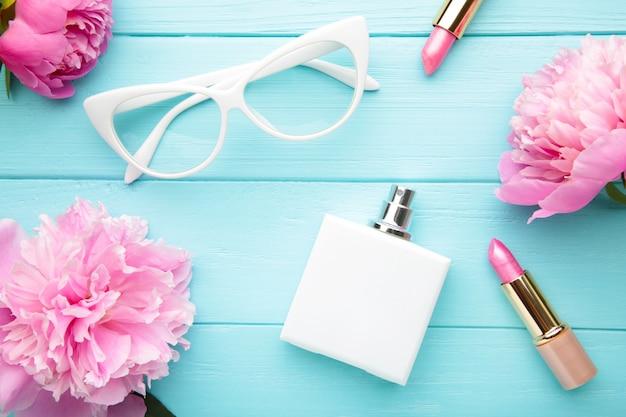 Make-up met glazen en bloemen op blauwe achtergrond, hoogste mening wordt geplaatst die.