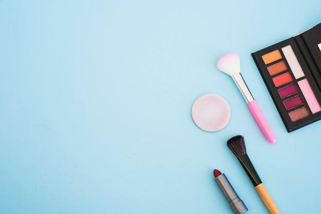 Make-up oogschaduw paletpenseel; spons; lippenstift op blauwe achtergrond