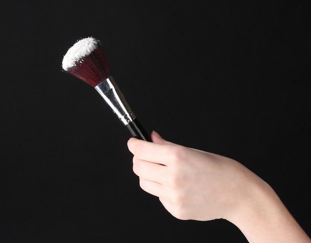 Make-up penseel met poeder geïsoleerd op zwart