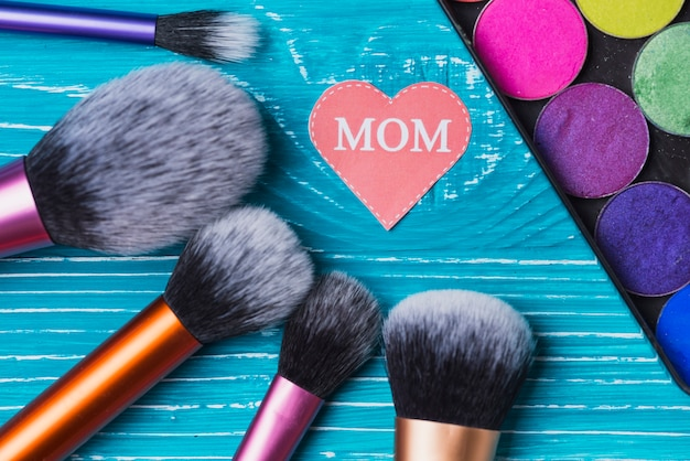 Make-up penselen, gekleurde poeders en document hart voor moederdag