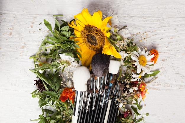 Make-up penselen op een stapel wilde bloemen op houten achtergrond
