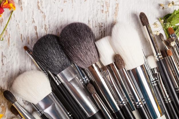 Make-up penselen op houten achtergrond naast wilde bloemen. professionele cosmetica