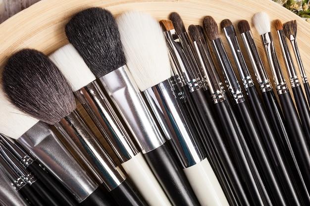 Make-up penselen op plaat naast wilde bloemen op houten achtergrond