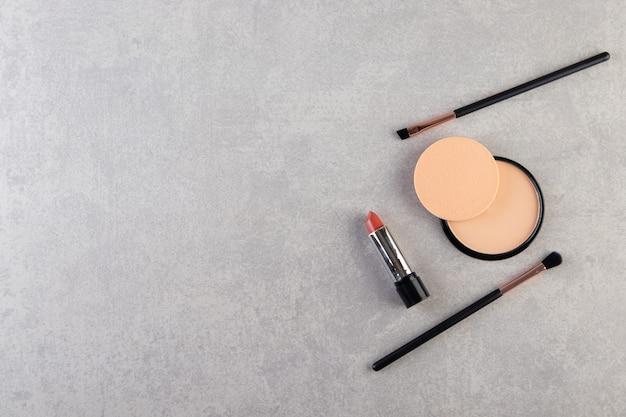 Make-up poeder in zwart rond plastic doosje met lippenstift en kwasten.