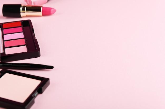 Make-up producten close-up op lichtroze achtergrond. oogschaduwpalet, gezichtspoeder, oogpotlood en lippenstift