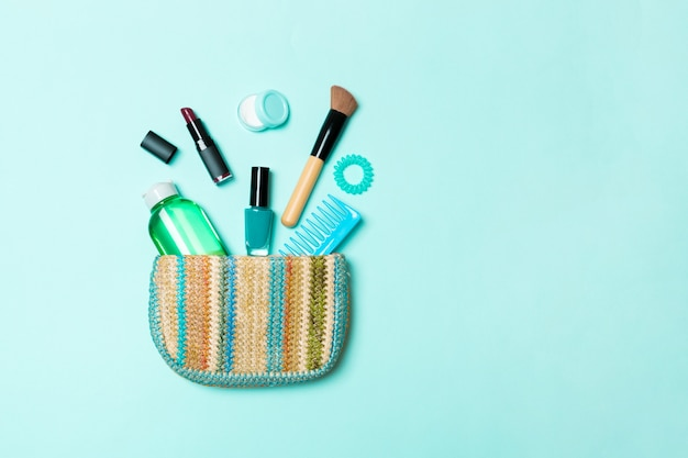 Make-up producten die uit een make-uptas op blauwe pastel komen met lege ruimte voor uw ontwerp