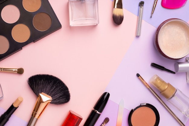 Make-up producten en cosmetica op multi kleur achtergrond, plat leggen. mode en beauty bloggen concept. bovenaanzicht