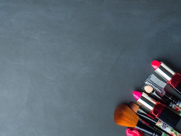 Make-up producten en gereedschappen met roze bloemblaadjes. achtergrond copyspace