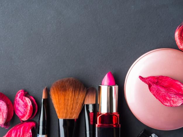 Make-up producten en gereedschappen met roze bloemblaadjes