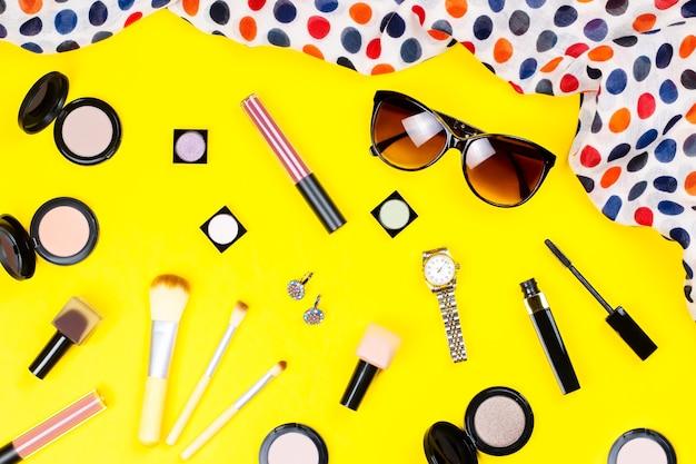 Make-up producten, sieraden, accessoires op geel