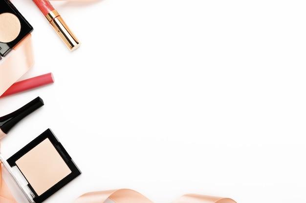 Make-up producten van bovenaf op witte achtergrond. rouge, poedercontainer voor het gezicht, nagellak en lipgloss
