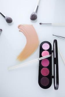 Make-up schaduwpalet met kwasten en een uitstrijkje foundation