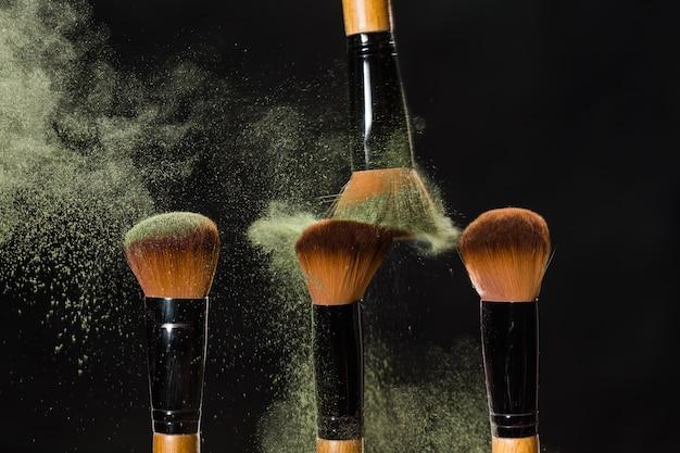Make-up, schoonheid en mineraal poeder concept - cosmetica borstel en explosie kleurrijke make-up poeder