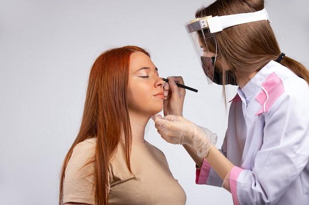 Make-up voor een meisje met lang rood haar. nieuw normaal schoonheidsconcept. make-up wordt gedaan door een meester in een medische mantel, masker, handschoenen en een beschermend scherm om de verspreiding van het virus te beschermen.