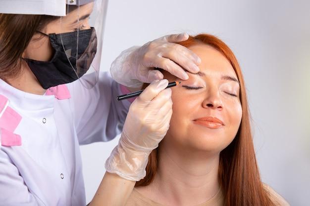 Make-up voor een meisje met lang rood haar, wordt gedaan door een meester gekleed in een medische mantel, masker, handschoenen en een beschermend scherm om het virus te beschermen. schoonheid en covid 19 concept.