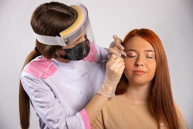 Make-up voor een roodharig meisje. een visagist in een medische jurk, masker en handschoenen. schoonheid en covid 19 concept.