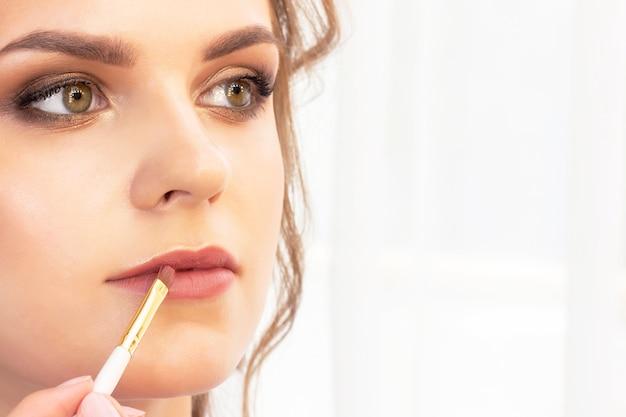 Make-upartiest brengt make-up op het model aan. lip verfborstel voor lippenstift.