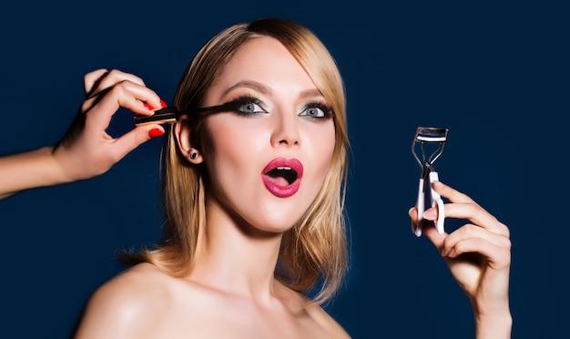 Make-upartiest brengt mascara aan op de wimpers.