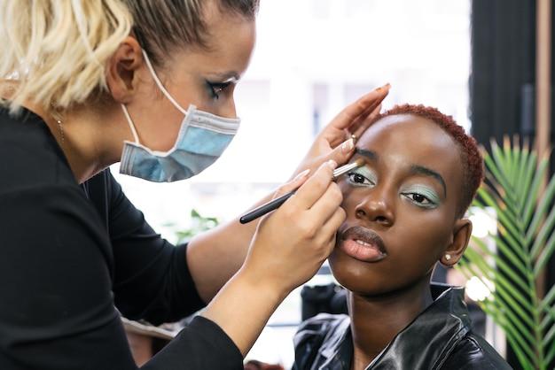 Make-upartiest die de ogen vormt van een vrouw met een masker dat de klant beschermt vanwege de coronavirus-pandemie covid 19 in een studio