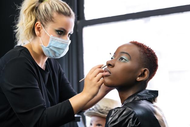 Make-upartiest die een vrouw bedenkt met een masker dat de klant beschermt vanwege de pandemie van coronavirus covid 19 in een studio