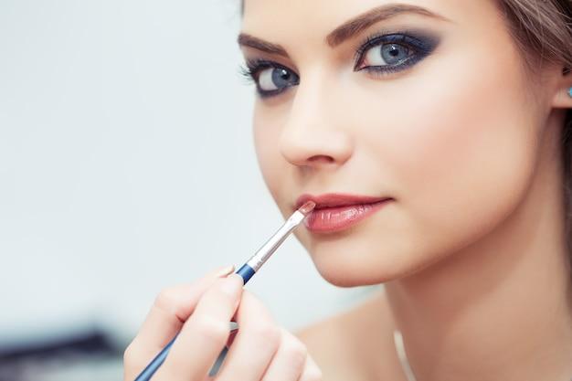 Make-upartiest die lippenstift met een borstel op modellenlippen toepast