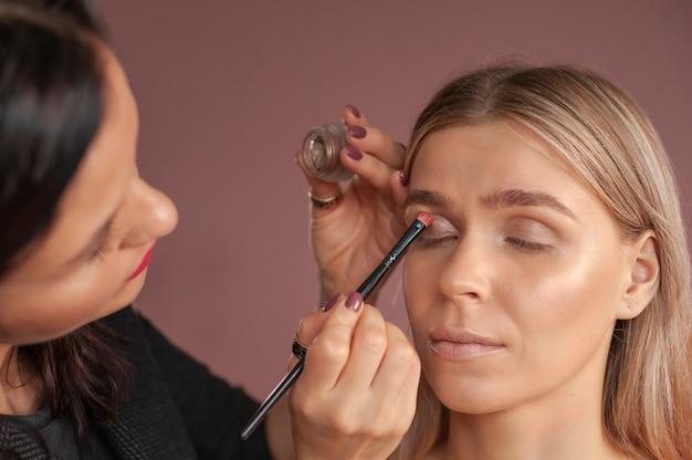 Make-upartiest gebruikt een penseel voor ogen en maakt smokey eyes. bruine oogschaduw.