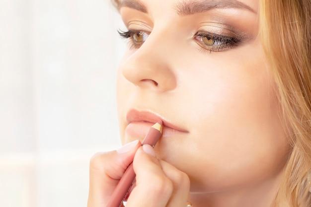 Make-upartiest maakt make-up op meisjesmodel. bruiloftsmake-up, avondmake-up, natuurlijke make-up. visagist schildert lippen van meisje