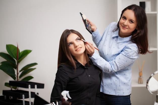 Make-upartiest maakt professionele make-up voor de klant bij haar thuis