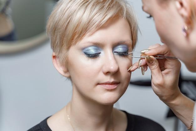 Make-upartiest plakt valse wimpers op model