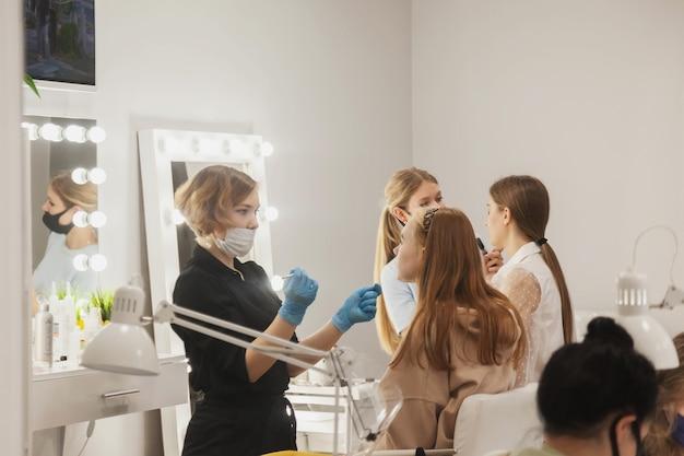Make-upartiesten vormen jonge vrouwen in de schoonheidssalon. klantenservice in de binnenruimte om een geweldig beeld te creëren. werk make-up creatie wizard. concept van stijl en meet tevredenheid. ruimte kopiëren