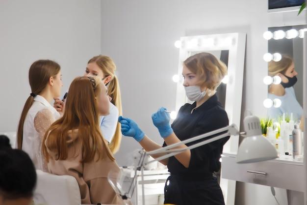 Make-upartiesten vormen jonge vrouwen in de schoonheidssalon.