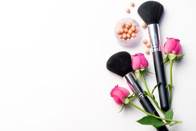 Make-upborstel, bloemen en bloos op een witte achtergrond. schoonheid concept. close-up met ruimte voor tekst