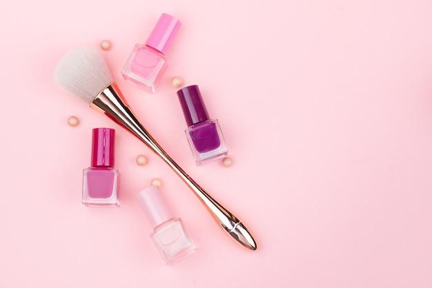 Make-upborstel en nagellakken op een roze achtergrond. close-up met ruimte voor tekst.