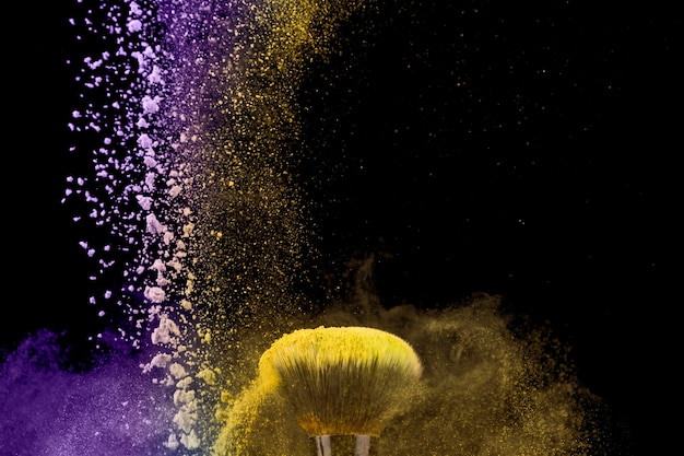 Make-upborstel en stof van poeder op donkere achtergrond