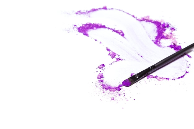 Make-upborstel en verkruimelde gemengde violette oogschaduw verschillende tinten ruimte voor tekst make-upachtergrond