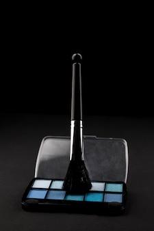 Make-upborstel in oogschaduw op donkere achtergrond