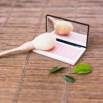 Make-upborstel met roze blusher en bladeren op placemat