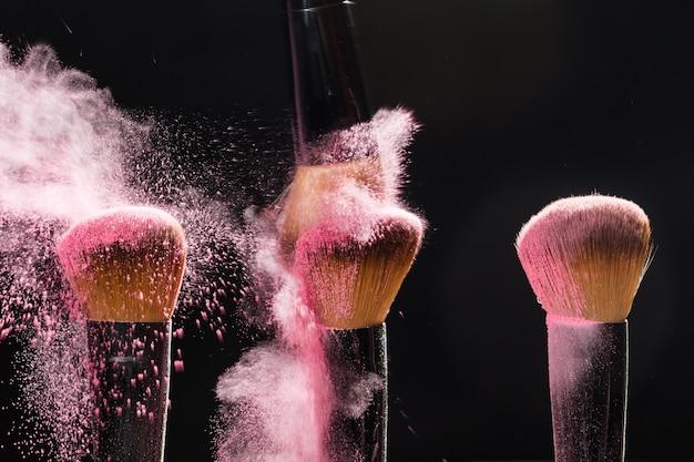 Make-upborstel met roze poederexplosie op zwarte muur.