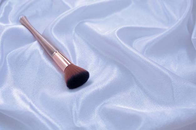 Make-upborstel op witte stof in golven