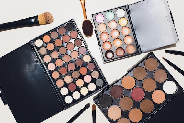 Make-upborstels en make-upoogschaduwen op een witte achtergrond.