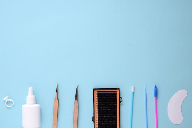 Make-upborstels en schoonheidsmiddelen op een blauwe achtergrond. bovenaanzicht, plat leggen, ruimte kopiëren