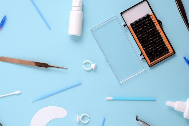 Make-upborstels en schoonheidsmiddelen op een blauwe achtergrond. bovenaanzicht, plat leggen