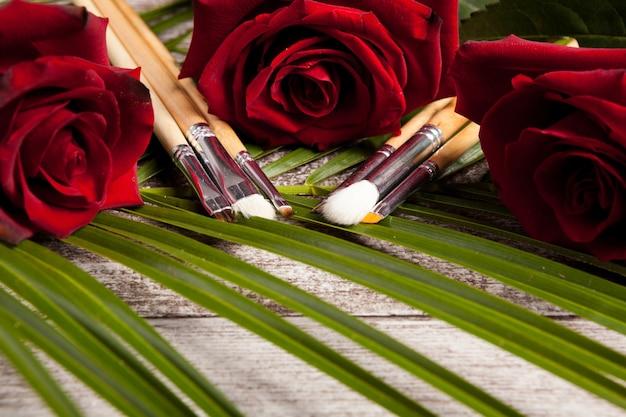 Make-upborstels naast rozen op houten achtergrond