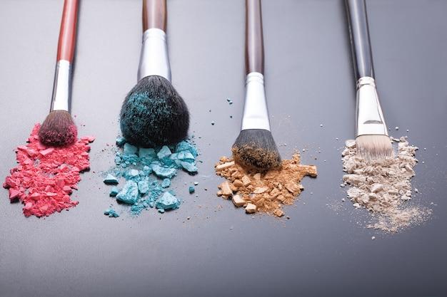 Make-upborstels op achtergrond met kleurrijk poeder.