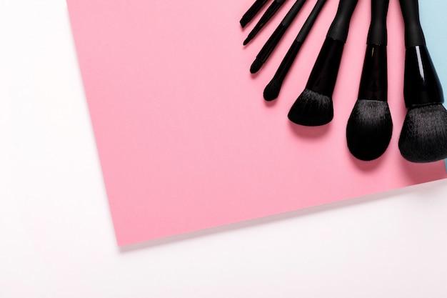 Make-upborstels op pastelkleurdocument roze achtergrond, hoogste mening