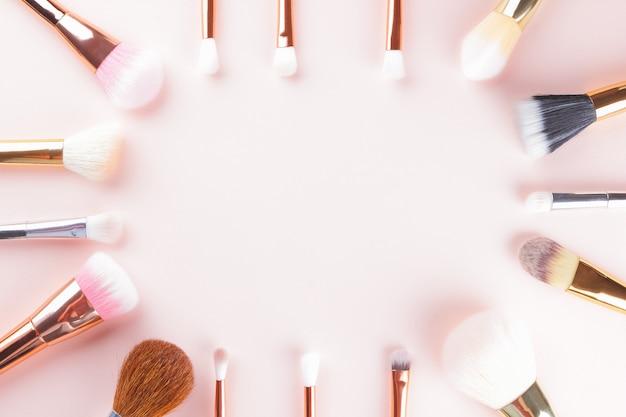 Make-upborstels op roze achtergrond. reeks gouden make-upborstels, concept. vrouwenschoonheidstoebehoren in pastelkleuren. kopieer ruimte. plat leggen