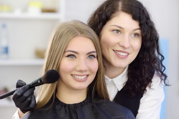 Make-upkunstenaar die de toon van de stichting met behulp van speciale borstel op gezicht van jong mooi model toepast