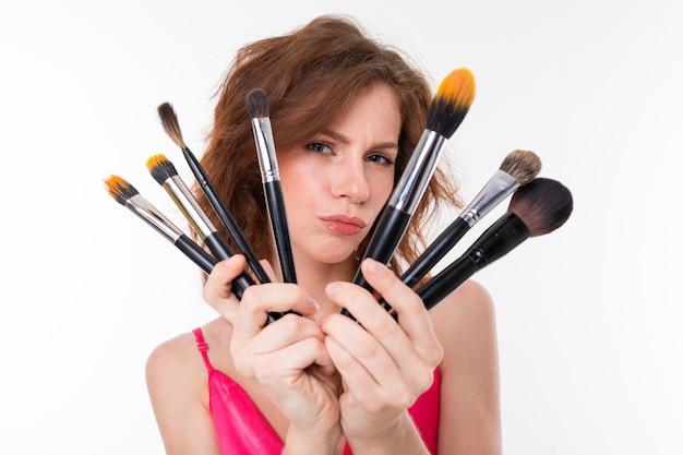 Make-upkunstenaar die een ventilator van heel wat make-upborstels op een witte muur houden