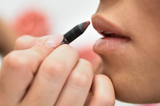 Make-upkunstenaar die omhoog lippen van een afrikaanse jonge vrouw maken